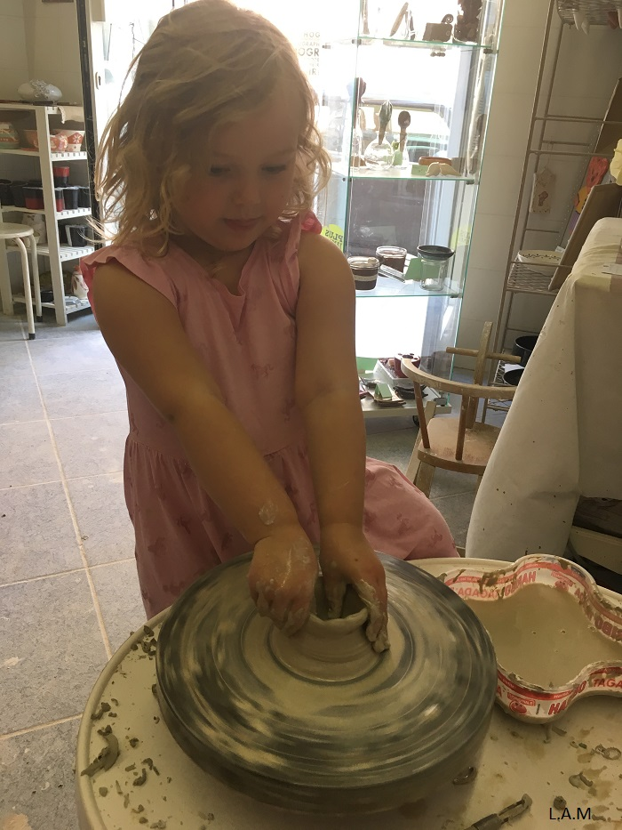 Girl thowing clay on a pottery wheel